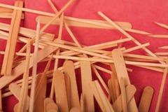 Los peque?os palillos de madera se mezclan en un fondo rojo fotografía de archivo