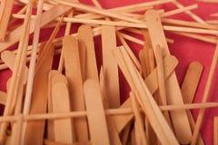 Los peque?os palillos de madera se mezclan en un fondo rojo fotos de archivo