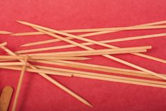 Los peque?os palillos de madera se mezclan en un fondo rojo imagen de archivo