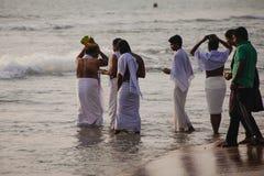 Los peregrinos caminan abajo al mar para ofrecer puja Imagenes de archivo