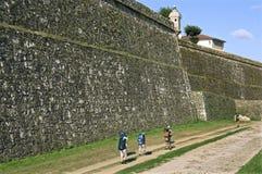 Los peregrinos caminan a lo largo de gigante, antiguo, pared de la ciudad, Valenã 8 Foto de archivo libre de regalías