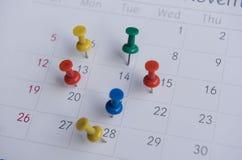 Los pernos coloridos del primer empujan la marca en un calendario Horario ocupado Imagenes de archivo