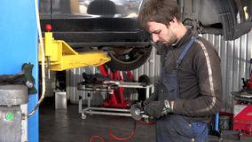 Los pernos oxidados de la rutina del hombre del trabajador del mecánico con la amoladora eléctrica equipan cerca del coche levant almacen de video