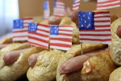 Los perritos calientes americanos con las pequeñas banderas americanas cierran plan, el bollo y la salchicha Imagen de archivo libre de regalías