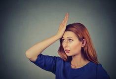 Los pesares perjudican hacer Mujer tonta, dando una palmada a la mano en la cabeza que tiene duh imágenes de archivo libres de regalías