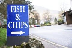 Los pescado frito con patatas fritas hacen compras la muestra para llevar Reino Unido del café foto de archivo