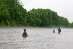 Los pescadores cogen el río de color salmón fotografía de archivo