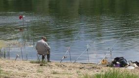 Los pescadores cogen pescados en el río con las cañas de pescar y el giro