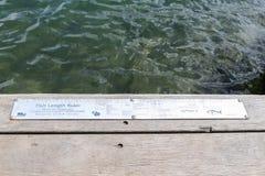 Los pescadores de la ayuda de las reglas de la longitud de los pescados cumplen con los límites l de la captura imagen de archivo