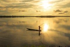 Los pescadores están echando un lago en la puesta del sol Fotografía de archivo