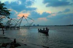 Los pescadores están lanzando redes chinas en el fuerte Kochi Imagenes de archivo