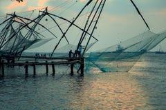 Los pescadores están lanzando redes chinas en el fuerte Kochi Imagen de archivo