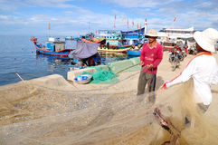 Los pescadores están quitando las anchoas pescan de sus redes para comenzar un nuevo día laborable en la isla del hijo de LY Imagenes de archivo