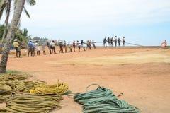 Los pescadores están tirando de la red del mar en la India Foto de archivo libre de regalías