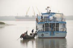 Los pescadores hablan con los personales de barco de cruceros turísticos en Mongla, Bangladesh foto de archivo
