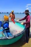 Los pescadores locales están preparando sus redes de pesca por un nuevo día laborable en la playa de Lagi Imágenes de archivo libres de regalías