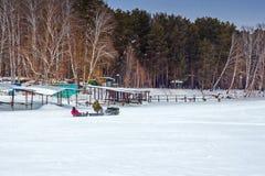 Los pescadores montan en una remolque de Moto con la pesca del invierno Fotos de archivo