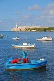 Los pescadores que trabajan en un pequeño barco azul con Morro se escudan en el fondo Imagen de archivo