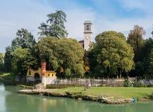 Los pescadores se relajan al lado de un churchtower en el ` Adda, Italia de Cassano d Imágenes de archivo libres de regalías