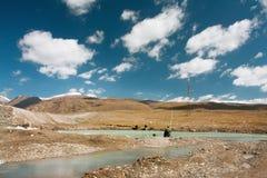 Los pescadores sientan y esperan los pescados que muerden en un río de la montaña en la mañana soleada Imagen de archivo