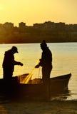 Los pescadores siluetean en la puesta del sol Imagen de archivo libre de regalías