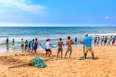 Los pescadores tiran de una red barredera con una captura en la playa en un día soleado Imagenes de archivo