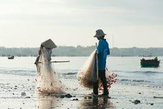 Los pescadores vietnamitas (hombre y mujer) doblan redes Fotos de archivo
