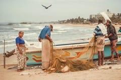 Los pescadores y las mujeres estiman la captura de pescados de redes del Océano Índico Fotografía de archivo