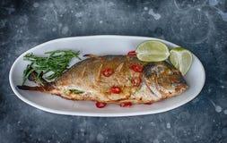 Los pescados asados a la parrilla con los chiles y el verde adornan Fotos de archivo libres de regalías