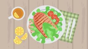 Los pescados asados a la parrilla sirvieron con las verduras, el té y los cubiertos fotos de archivo