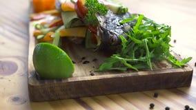 Los pescados asaron a la parrilla con las verduras frescas y las especias en el tablero de madera La composición de los alimentos almacen de video