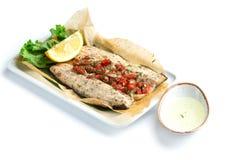 Los pescados cocidos cortan con paprika en el fondo blanco fotografía de archivo