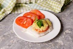 Los pescados cocieron con queso y tomates en una placa blanca Fotografía de archivo