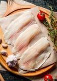 Los pescados de la Tilapia cortan en una tabla de cortar con los clavos, los tomates y el tomillo de ajo imágenes de archivo libres de regalías