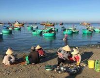 Los pescados de la venta de las mujeres en la playa en Phan sonaron, Vietnam Foto de archivo