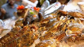 Los pescados de mar frescos, cangrejos, los diversos mariscos se venden en el contador de la tienda en la calle almacen de metraje de vídeo