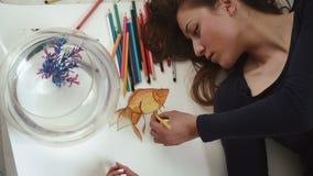 Los pescados de oro de la chica joven del drenaje hermoso del artista se cierran para arriba en la visión superior metrajes