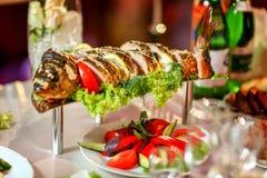 Los pescados rellenos grandes con las verduras adornaron las hierbas en la tabla Fotografía de archivo