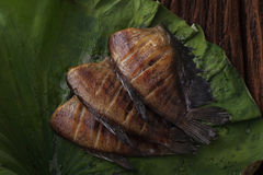 Los pescados salados secados comida tailandesa de la damisela frieron con la decoración del loto de la licencia en fondo de mader Imagen de archivo libre de regalías