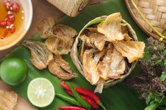 Los pescados secados al sol curruscantes fritos sobre plátano verde hojean Comida asiática d Imagenes de archivo