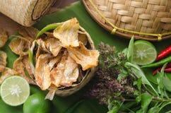 Los pescados secados al sol curruscantes fritos sobre plátano verde hojean Comida asiática d Foto de archivo libre de regalías