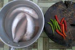 los pescados y el chile se preparan para la cena foto de archivo