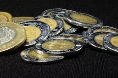 Los Pesos acuñan en una pila con el fondo negro Foto de archivo