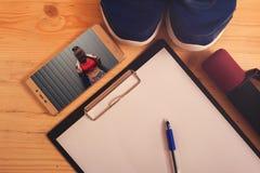 Los pesos, zapatillas de deporte, se divierten el sujetador, tablero con la pluma Imagenes de archivo