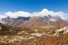 Los picos de la nieve de la montaña de Ama Dablam cubrieron las nubes Foto de archivo libre de regalías