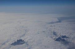 Los picos de las montañas alpinas en la opinión de las nubes del pl Fotografía de archivo libre de regalías