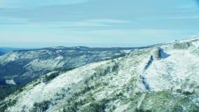 Los picos de montaña nevados en naturaleza salvaje del invierno asombroso ajardinan en la antena 4k metrajes