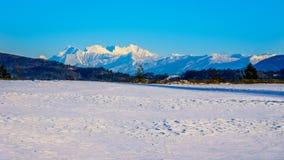 Los picos nevados de la montaña de oro de los oídos detrás de la ciudad del fuerte Langley en Fraser Valley Imágenes de archivo libres de regalías