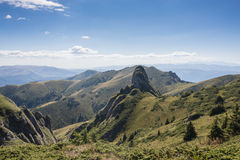 Los picos rocosos dramáticos fijaron contra una cordillera y un cielo azul Foto de archivo libre de regalías