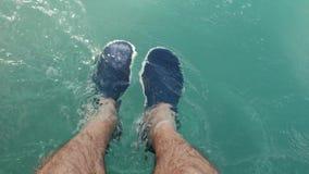 Los pies de los hombres en el mar y en deslizadores metrajes